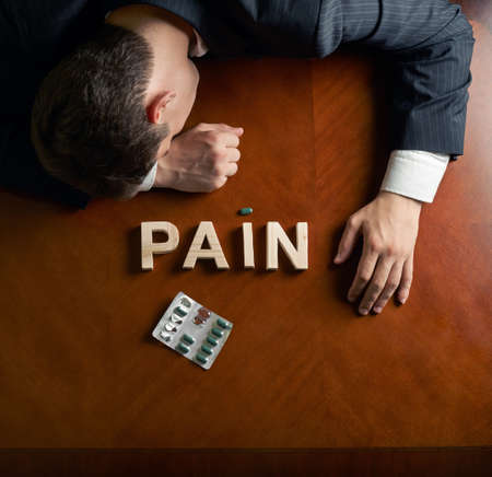 devastated: Word Pain made of wooden block letters and devastated middle aged caucasian man in a black suit sitting at the table, top view composition with dramatic lighting