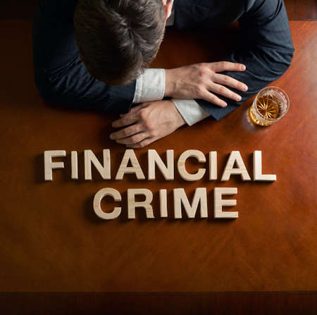 devastated: Phrase Financial Crime made of wooden block letters and devastated middle aged caucasian man in a black suit sitting at the table with the glass of whiskey, top view composition with dramatic lighting