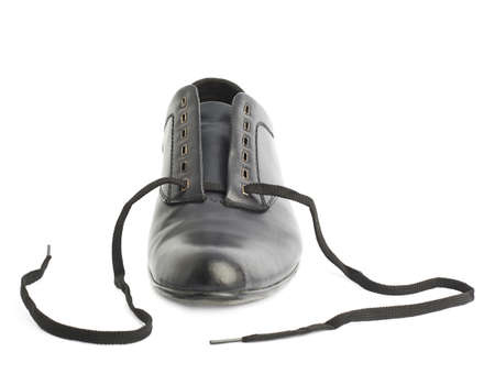 untied: Classic black leather shoe with untied shoelaces, isolated over the white background