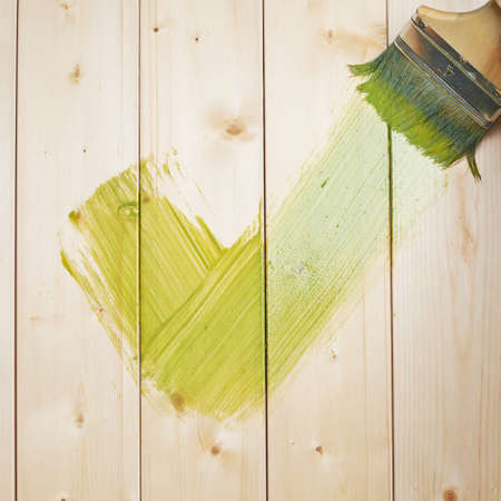 Green yes tick symbol drawn with the wide brush over the polished pine wood boards photo