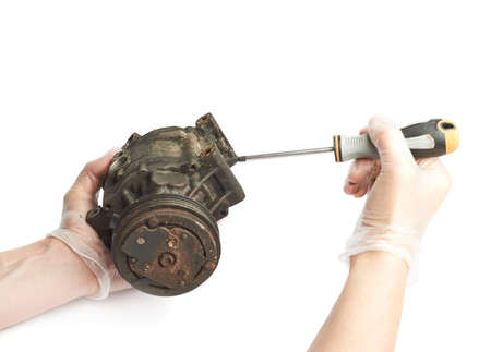 disassembly: Disassembly of the engine mechanism element by hands and screwdriver, isolated over the white background