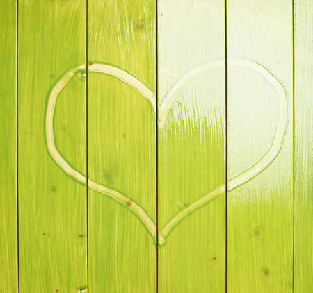 recently: Heart drawn with the finger over the recently painted green wood boards Stock Photo