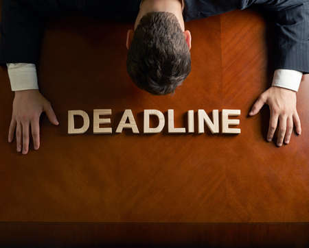 devastated: Word Deadline made of wooden block letters and devastated middle aged caucasian man in a black suit sitting at the table, top view composition with dramatic lighting