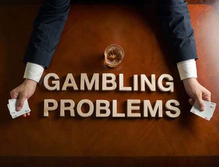 gambling: Phrase Gambling Problems made of wooden block letters and devastated middle aged caucasian man in a black suit sitting at the table with the glass of whiskey, top view composition with dramatic lighting