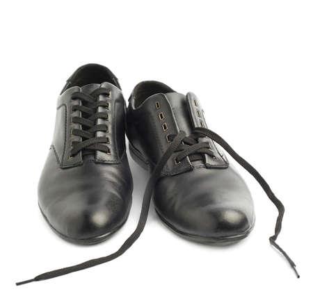untied: Composici�n de dos zapatos cl�sicos negros de cuero, una con cordones de los zapatos desatados, aislados sobre el fondo blanco Foto de archivo