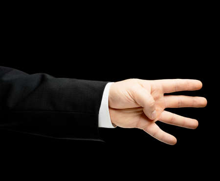 lowkey: Caucasian male hand in a business suit showing number four with fingers, low-key lighting composition, isolated over the black background