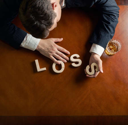 devastated: Word Loss made of wooden block letters and devastated middle aged caucasian man in a black suit sitting at the table with the glass of whiskey, top view composition with dramatic lighting