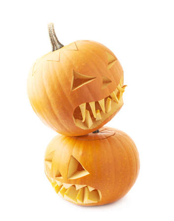 Two Jack-o-lanterns orange pumpkin heads placed one over another, composition isolated over the white background photo