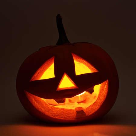 lowkey: Jack-o-lanterns orange halloween pumpkin head with the light glowing from the inside, dark low-key composition Stock Photo
