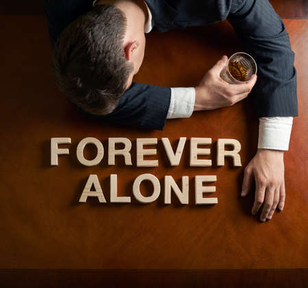 devastated: Phrase Forever Alone made of wooden block letters and devastated middle aged caucasian man in a black suit sitting at the table with the glass of whiskey