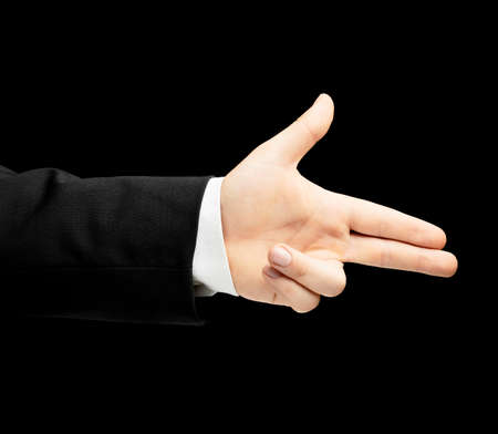 lowkey: Caucasian male hand in a business suit, pointing gun gesture sign, low-key lighting composition, isolated over the black background