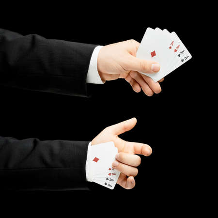 4 of a kind: Caucasian male hand in a business suit, holding ace playing cards in the sleeve, low-key lighting composition, isolated over the black background