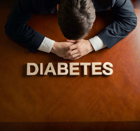 devastated: Word Diabetes made of wooden block letters and devastated middle aged caucasian man in a black suit sitting at the table, top view composition with dramatic lighting Stock Photo