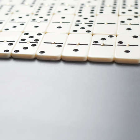gambling counter: Multiple domino bones over the dark gray surface as a background composition with the shallow depth of field