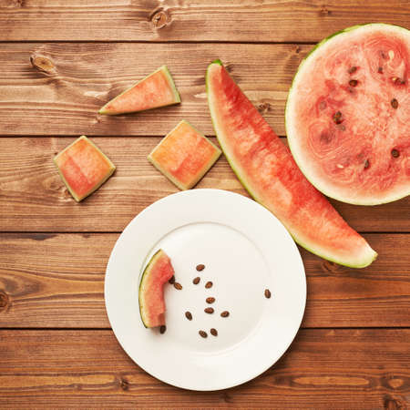 eaten: Slices of eaten watermelon in and next to a white ceramic plate, composition over the surface made of brown wooden boards