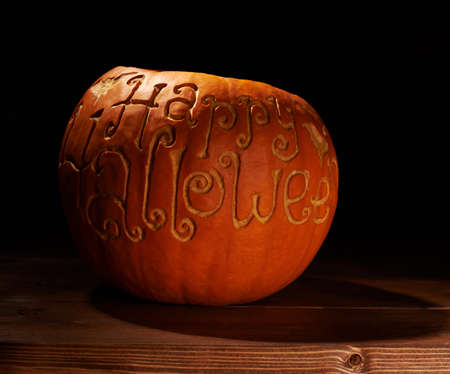 low key lighting: Pumpkin with the words Happy Halloween carved on its surface, placed over the wooden boards in a low key lighting composition