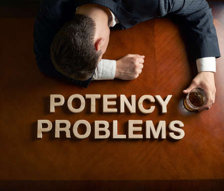 potency: Phrase Potency Problems made of wooden block letters and devastated middle aged caucasian man in a black suit sitting at the table with the glass of whiskey, top view composition with dramatic lighting