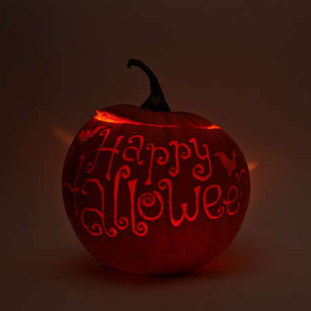 lowkey: Happy halloween words carved on Jack-o-lanterns orange halloween pumpkin with the light glowing from the inside, dark low-key composition Stock Photo