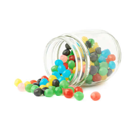 Colorful candy ball sweets falling out of a glass jar, composition isolated over the white background Imagens