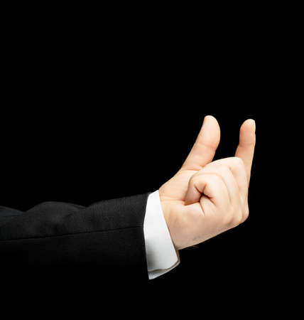 decreasing in size: Caucasian male hand in a business suit, showing the size with two fingers gesture sign, low-key lighting composition, isolated over the black background