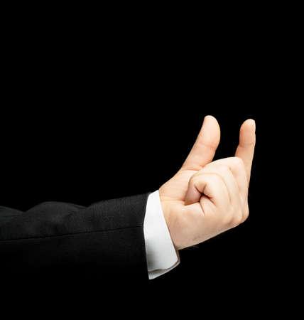 decreasing in size: Caucasica mano maschile in un tailleur, che mostra le dimensioni con due dita il gesto segno, low-key composizione illuminazione, isolato su sfondo nero Archivio Fotografico