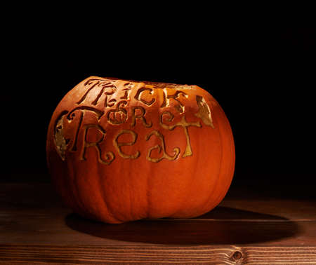 low key lighting: Halloween pumpkin with the words Trick or Treat carved on its surface, placed over the wooden boards in a low key lighting composition Stock Photo