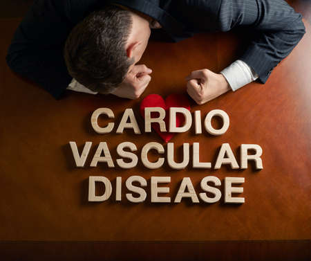 Phrase Cardio Vascular Disease made of wooden block letters and devastated middle aged caucasian man in a black suit sitting at the table with the red symbolic heart, top view composition with dramatic lighting photo