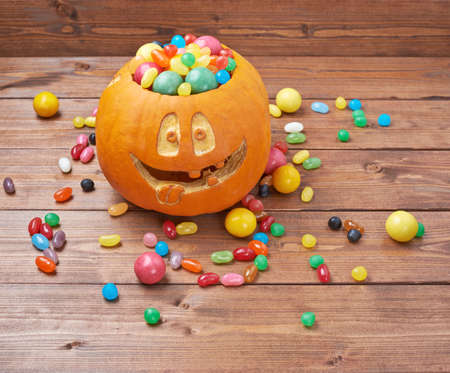 Jack o lantern halloween pumpkin filled with multiple colorful sweets and candies over the wooden board background composition Stock Photo