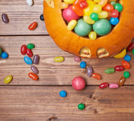 Jack o lantern halloween pumpkin filled with multiple colorful sweets and candies over the wooden board background composition, top view above foreshortening photo