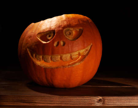 low key lighting: Scary jack o lantern halloween pumpkin over the wooden boards surface, in a low key lighting composition