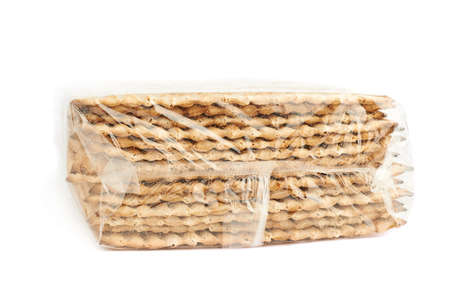 matza: Pile of unopened wrapped in plastic machine made matza flatbread, composition isolated over the white background