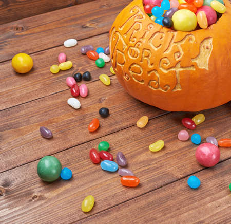 Halloween pumpkin with the words trick or treat carved over its surface and filled with multiple sweets and candies, composition over the wooden board background