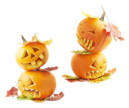 Two Jack-o-lanterns orange pumpkin heads placed one over another and covered with colorful maple leaves, composition isolated over the white background, set of two foreshortenings photo