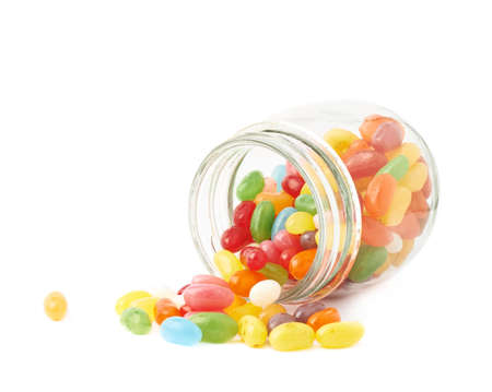 Colorful jelly bean candy sweets spilled out of a glass jar, composition isolated over the white background photo