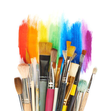 Pile of the multiple different brushes over the rainbow gradient paint strokes, composition isolated over the white surface, top view above Stock Photo