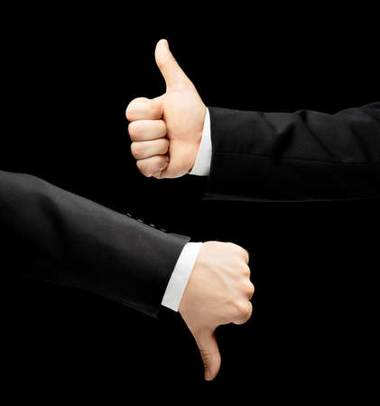Caucasian male hand in a business suit, showing thumbs up and down gesture signs, low-key lighting composition, isolated over the black background