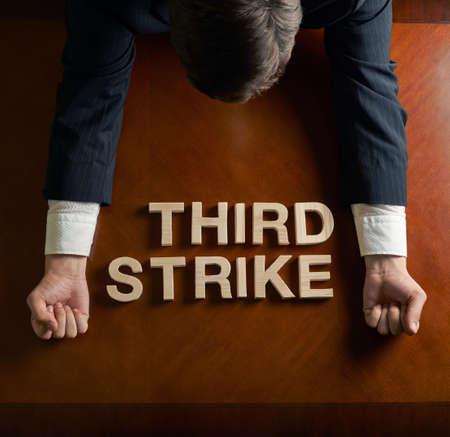 devastated: Phrase Third Strike made of wooden block letters and devastated middle aged caucasian man in a black suit sitting at the table, top view composition with dramatic lighting Stock Photo