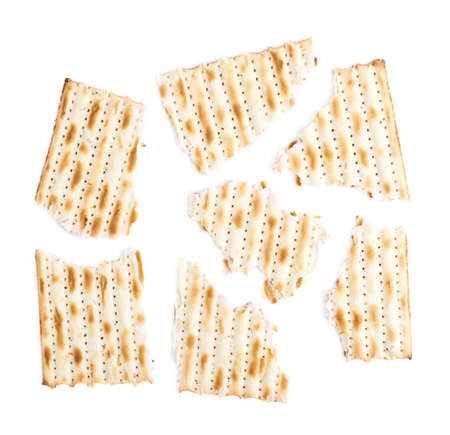 machine made: Cracked in multiple pieces machine made matza flatbread, composition isolated over the white background