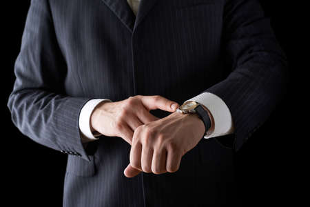 face shot: Pointing to the clock face shot of a caucasian man in a business suit, low-key dramatic light composition