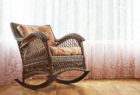 Brown wicker rocking chair against the windows curtains, indoor composition photo