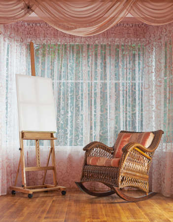 Copyspace empty white canvas on the wooden easel and next to wicker rocking chair, composition against the windows curtains background photo