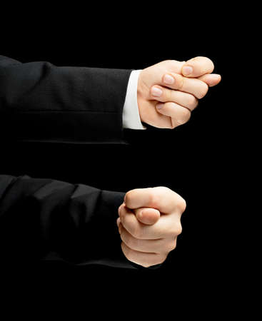 Caucasian male hand in a business suit, showing the offensive fig gesture sign, low-key lighting composition, isolated over the black background, set of two images