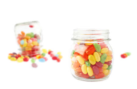 Composition of a glass jar and multiple colorful jelly bean candies, isolated over the white background photo