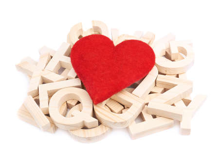 Passion for reading as a composition of the red heart over the pile of multiple wooden letters, isolated over the white background photo