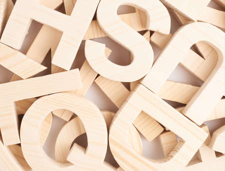 Surface covered with multiple wooden letters as a background composition photo