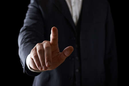 Pointing finger close-up shot of a caucasian man in a business suit, low-key dramatic light composition photo