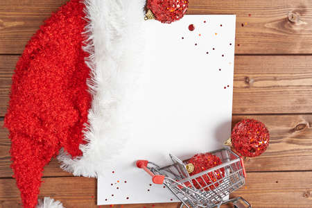 Christmas shopping list composition of the copyspace blank sheet of paper next to the small shopping cart and decorations over the wooden surface