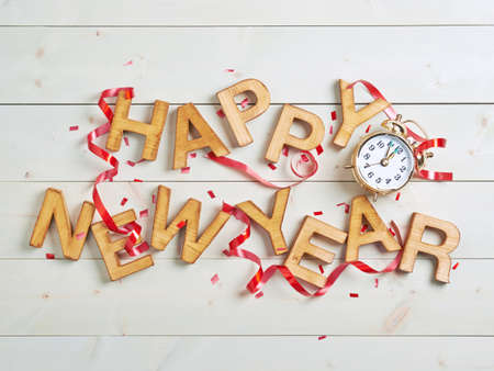 Happy New Year composition of the wooden letters surrounded with the multiple decorations over the white colored wooden boards surface