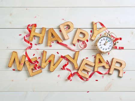 Gelukkig Nieuwjaar samenstelling van de houten letters omringd met de vele versieringen boven de wit gekleurde houten planken oppervlak