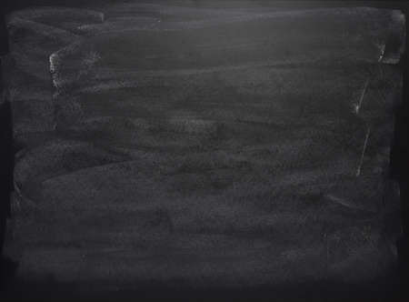 Black board with the traces of chalk over its surface as a background texture Imagens